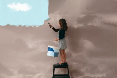 Obraz little girl uses a can of paint to color the wall of the room from cloudy gray to clear blue sky - positive attitude, vibes and mentality concept