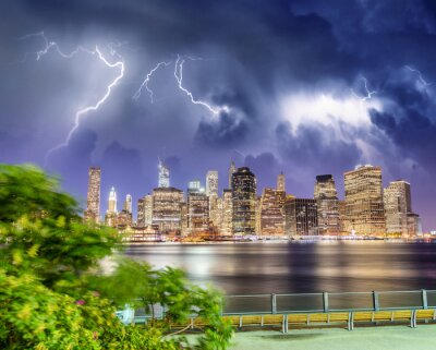 Lower Manhattan night skyline with storm approaching. East River Downtown skyscrapers lights reflections, New York City - USA