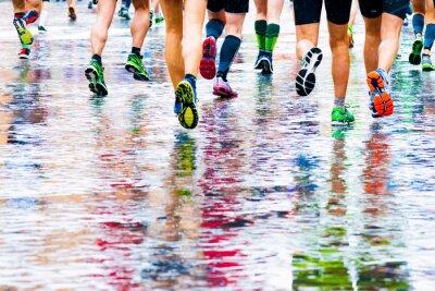Obraz Ludzie, którzy uruchomili w maratonie na zwilżonej powierzchni