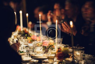 Obraz Ludzie lubią rodzinny obiad przy świecach. Duży stół z jedzeniem i napojami.