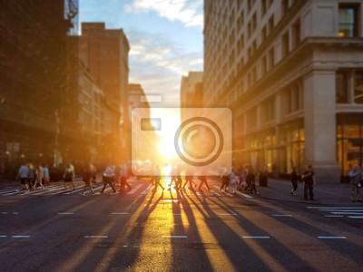 Ludzie przechodzą przez ruchliwe skrzyżowanie na 23 ulicy na Manhattanie w Nowym Jorku z kolorowym światłem zachodu słońca rzucającym długie cienie
