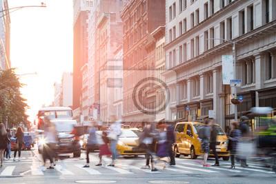 Ludzie w ruchu przez ruchliwie skrzyżowanie w Miasto Nowy Jork z światła słonecznego tłem