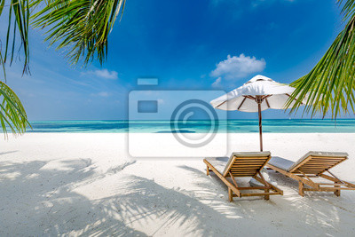 Obraz Luxury beach resort, beach loungers near the sea with white sand over sea Topical island background, summer vacation concept, holiday and tourism design. Exotic landscape, inspirational leisure banner