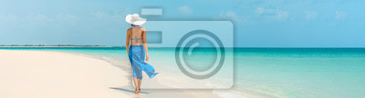 Obraz Luxury beach vacation elegant tourist woman walking relaxing in beachwear hat on white sand Caribbean beach. Lady tourist on holiday vacation resort. Banner panorama landscape.