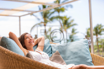 Obraz Luxury hotel home living woman relax enjoying sofa furniture of outdoor patio. Beautiful young multiracial Asian girl relaxing day dreaming for rich early retirement in getaway tropical house.