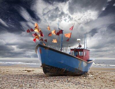 Mała łódź rybacka na brzegu Morza Bałtyckiego.