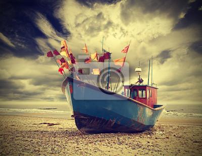 Mała łódź rybacka na wybrzeżu Morza Bałtyckiego, zabytkowe retro ins