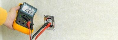 Obraz Male electrician checks the voltage of an outlet on a white wall with a multimeter in the house close up. Banner
