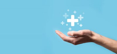 Obraz Male hand holding plus icon on blue background. Plus sign virtual means to offer positive thing like benefits, personal development, social network Profit,health insurance, growth concepts