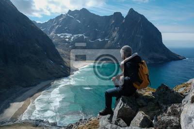 Obraz Man sitting on cliff edge alone enjoying aerial view backpacking lifestyle travel adventure outdoor vacations in Norway top of Reinebringen mountain.