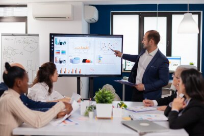 Obraz Manager holding briefing presentation in conference room monitor project. Corporate staff discussing new business application with colleagues looking at screen