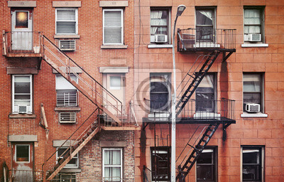 Manhattan old residential buildings with fire escapes, color toning applied, New York City, USA.