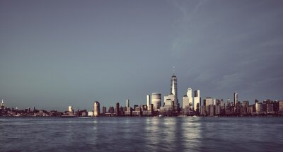 Manhattan panoramic skyline with buildings reflecting last sunlight, color toning applied, New York City, USA.