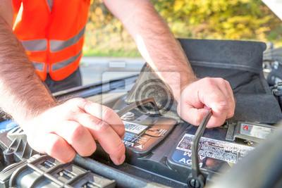Mann checkt Autobatterie