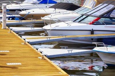 Marina z zacumowanymi jachtami i motorówkami.