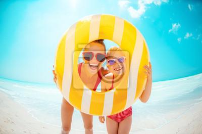 Obraz matka i dziecko patrząc przez żółty nadmuchiwane koło ratunkowe