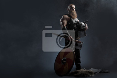 Obraz Medieval warrior berserk Viking with tattoo with axes attacks enemy. Concept historical photo