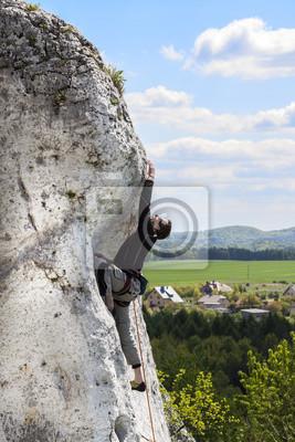 Mężczyzna wspina naturalną trudną skaliste ściany.