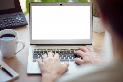 Obraz Mężczyzna z laptopem przy biurowym biurkiem z pustym ekranem