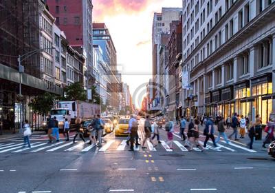 MIASTO NOWY JORK, CZERWIEC, 2018: Tłumy różnorodnych ludzi krzyżują ruchliwe skrzyżowanie przy 23 ulicy i 5 Avenue na Manhattanie z ruchem w godzinach szczytu w tle.
