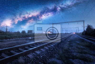Milky Way over the railway station at starry night. Beautiful industrial landscape with blue sky and stars, galaxy, railroad and buildings at dusk. Railway platform and space in summer. Technology