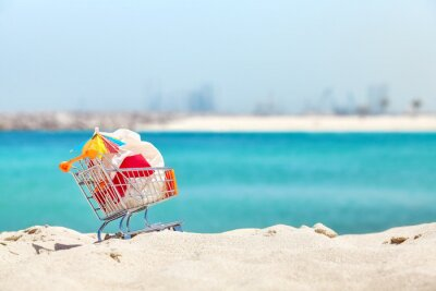 Miniaturowy koszyk z plastikową torbą i koktajl parasol po stronie turystycznej na tropikalnej plaży, zanieczyszczenie środowiska koncepcji obrazu.