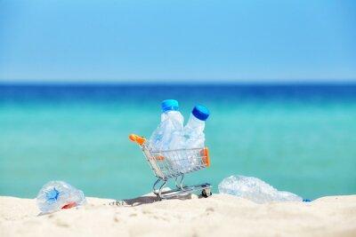Miniaturowy koszyk z pustymi plastikowymi butelkami pozostawiony przez turystów na tropikalnej plaży, zanieczyszczenie środowiska koncepcji obrazu, selektywne fokus.