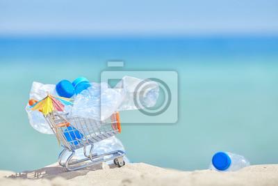 Miniaturowy wózek na zakupy z pustymi plastikowymi butelkami opuszczał turystą na tropikalnej plaży, zanieczyszczenia środowiska pojęcia obrazek, selekcyjna ostrość.