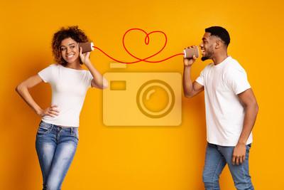 Obraz Młoda czarna para z puszka telefonem na pomarańczowym tle