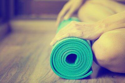 Obraz Młoda kobieta gospodarstwa matę do jogi