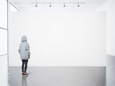 Obraz Młoda kobieta idzie w nowoczesnej galerii i patrząc na pustym płótnie