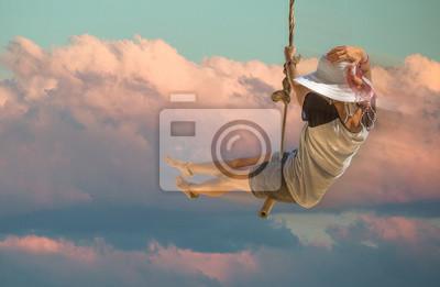 Obraz Młoda kobieta w krótkich spodenkach, koszulce i kapelusz z szerokim rondem swinging z zachodem słońca niebo i chmura tle. Pojęcie wolności.
