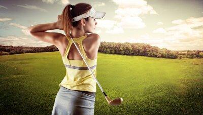 Obraz Młoda kobieta w sportowej gry w golfa na zielonym polu