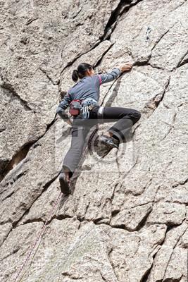 Młoda kobieta wspinaczki trudną ścianę.