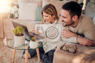 Obraz Młoda para relaksujący na kanapie z laptopem