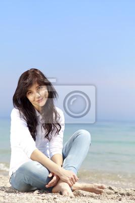 Młoda piękna brunetka dziewczyna na plaży w czasie wiosny. Przelicytować