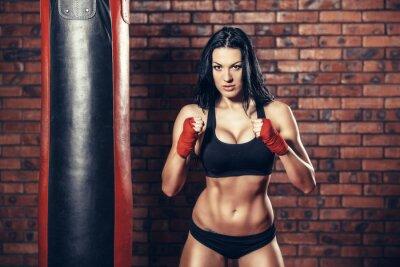 Obraz Młoda piękna seksowna kobieta bokser z czerwonym boksie bandaż na ręce. worek treningowy. mur z cegły w tle