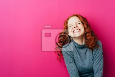 Obraz Młoda roześmiana kobieta przeciw różowemu tłu