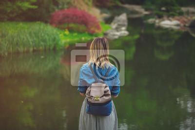 Młoda stylowa dziewczyna odpocząć w ogrodzie japońskim wiosną w pobliżu stawu