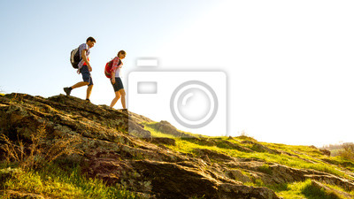 Obraz Młoda szczęśliwa para piesze wycieczki z plecakami na piękny skalisty szlak w słoneczny wieczór. Rodzinna podróż i przygoda.