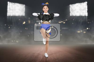Obraz Młody azjatykci cheerleader w akci z pom poms