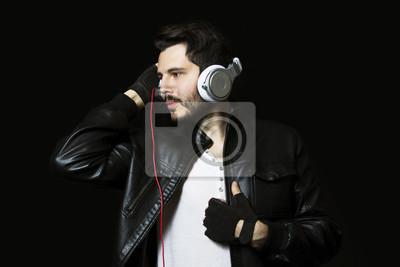 Obraz Młody człowiek słuchając muzyki na czarnym tle. przystojny młody