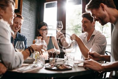Obraz Młody człowiek z przyjaciółmi w restauracji
