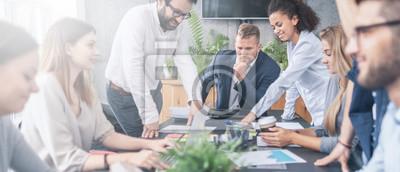 Obraz Młodzi kreatywnie ludzie biznesu spotyka przy biurem.