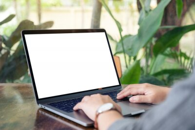 Obraz Mockup image of a woman using and typing on laptop with blank white desktop screen on wooden table