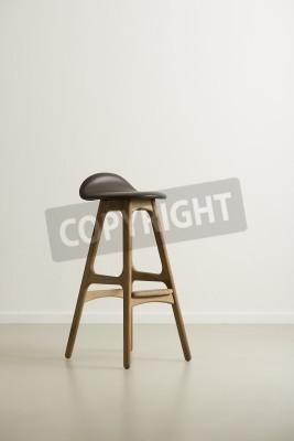Moderrn wysoki drewniany stołek barowy z czarnym skórzanym fotelu i podnóżki na odblaskowe piętrze w pustym pokoju z białej ścianie, formacie pionowym z copyspace w świetle dziennym