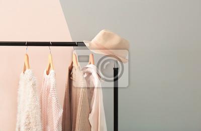 Obraz Morela i beżowa odzież na wieszaki przed modnym kolorem tła