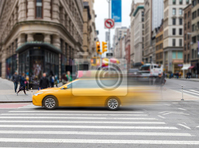 Motion blur of yellow taxi cab speeding through an intersection on 23rd Street in Midtown Manhattan New York City