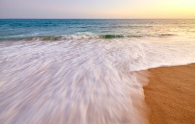 Motion blurred wave entering sandy beach at sunset.