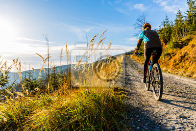 Obraz Mountain biking woman riding on bike in summer mountains forest landscape. Woman cycling MTB flow trail track. Outdoor sport activity.